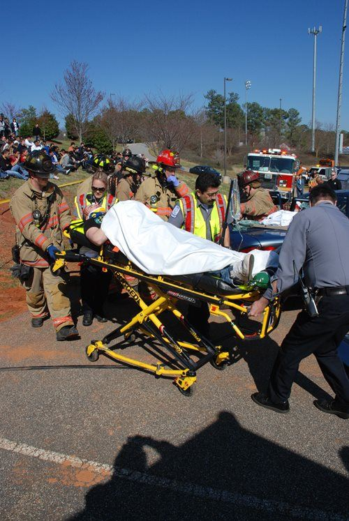 A group of firefighters pushing a person on a stretcher