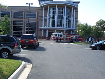 People standing outside of a building next to a fire truck as part of an evacuation drill