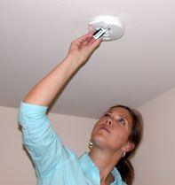 A woman changing the batteries in a smoke detector