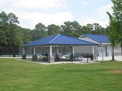 The Tumlin Park Pavilion with tables underneath it and trees in the background