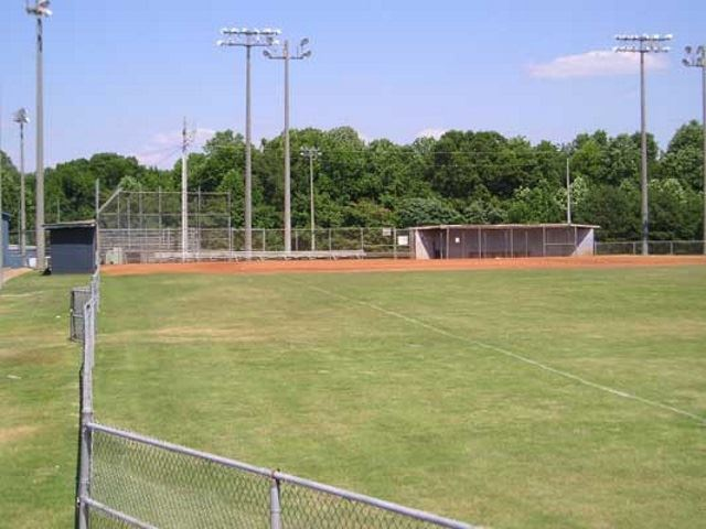 A baseball / softball field with trees in the background