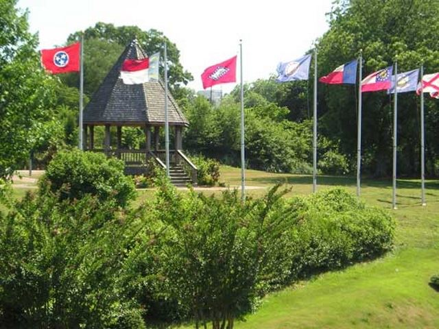8 flags with a gazebo in the background