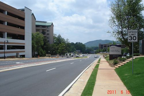 A large four lane road with a median, there are buildings on the left side and trees on the right si