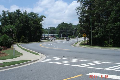 A wide intersection with trees surrounding it