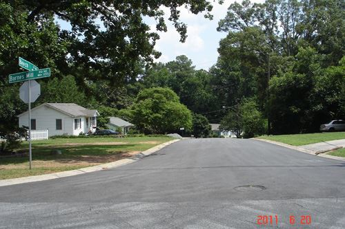 An intersection with a house and trees in the background