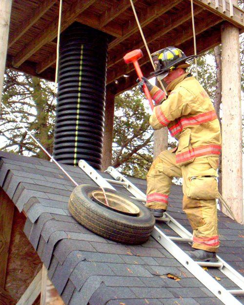 A firefighter on a roof simulator while standing on a ladder with a fake ax next to a tire
