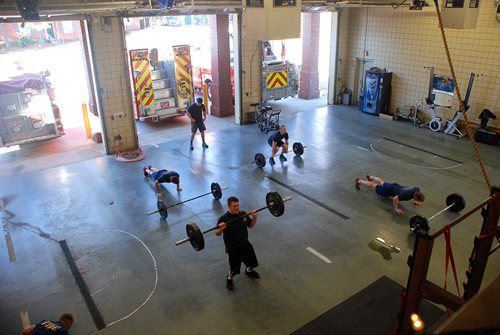 A group of firefighters lifting weights and doing other CrossFit training in a fire station