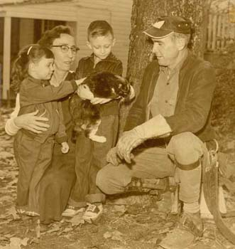 A black and white photo of a man and a woman with two kids holding a cat