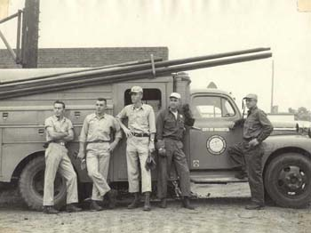 A black and white photo of five men standing in front of a truck