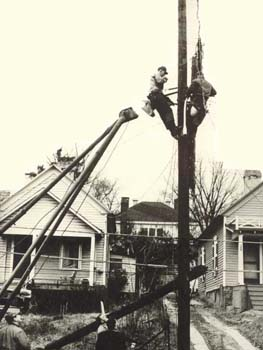 A black and white photo of two workers working on an electrical pole