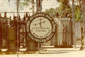 A black and white photo of the Board of Lights and Water Electrical Department sign