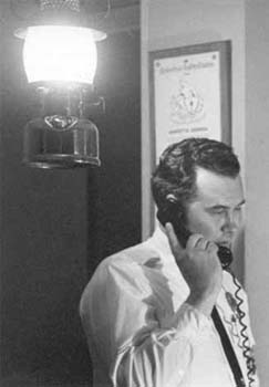 A black and white photo of a man on the phone