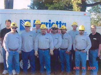 A group of ten workers wearing hard hats in front of a truck